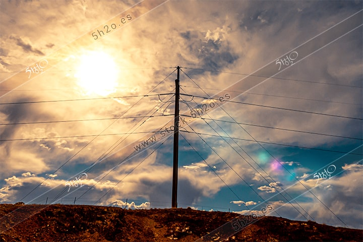 Foto de stock - Photo Stock - Poste electrico con sol tras las nubes