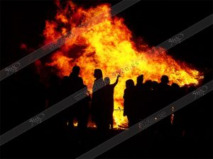 Gente en San Juan a cotraluz de la hoguera