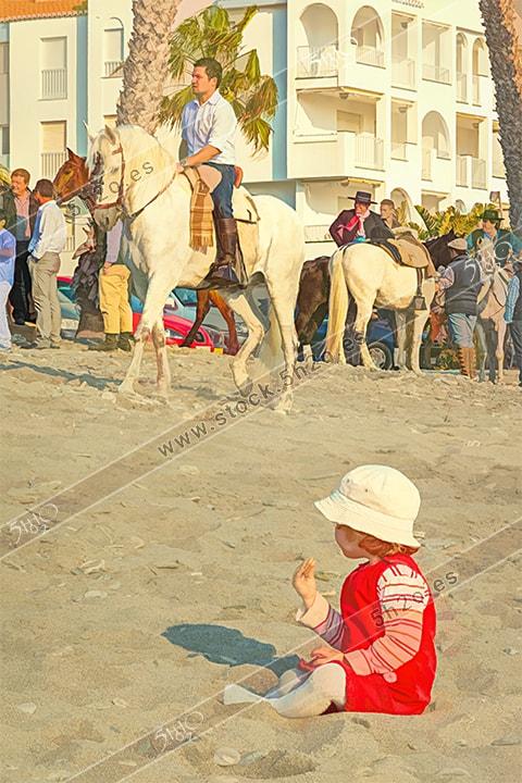 Jinetes en la arena con bebe en el suelo