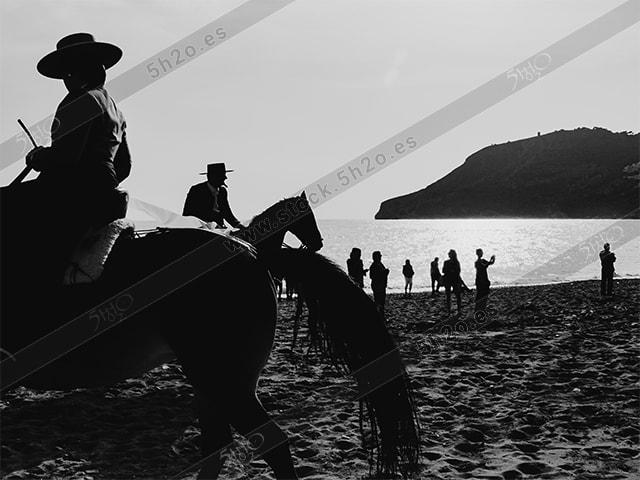 jinetes y gente en la orilla del mar