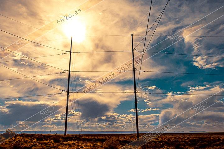 Foto de stock - Photo Stock - postes electricos con sol bajo de nubes