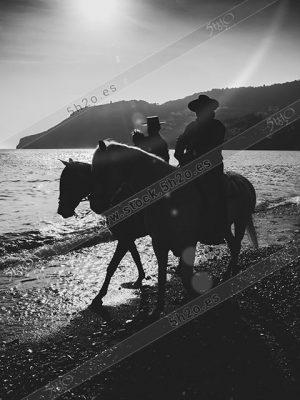 Foto de stock - Photo Stock - dos jinetes al paso por la playa en blanco y negro